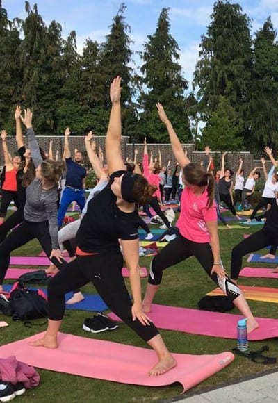 Large group doing outdoor yoga classes image 2