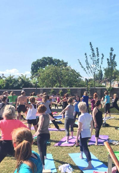 Large group doing outdoor yoga classes image 3